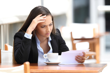 Worried executive reading letter in a coffee shop