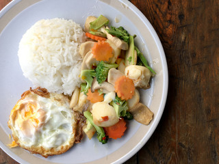 mixed fried vegetable tofu with rice and fried egg in white dish on wooden background. Vegetarian Food, healthy food.