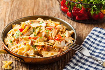 Pasta farfalle with chicken and paprika, in carbonara sauce.
