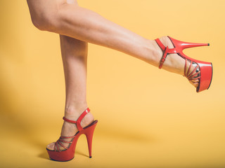 Woman in red stripper heels on yellow