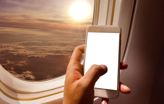 Asian man hand holding smart-phone start up working  on board of airplane near window seat and wing
