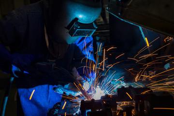 Industrial worker is welding in automotive part factory