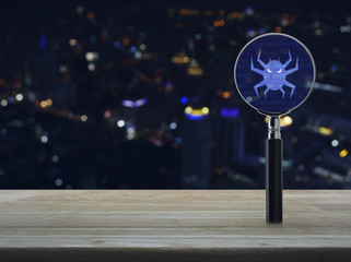 Virus computer icon with magnifying glass on wooden table over blur colorful night light city tower background, Business internet security concept
