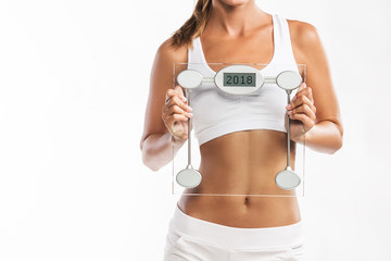 Close up of woman's abdomen, holding a weight scale with a year 2018 written on it - New Year's weigh t loss resolution