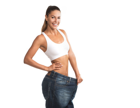 Fit, beautiful, young woman in oversize pants smiling, isolated on white background
