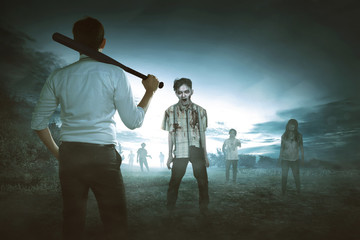 Back view of asian man holding baseball bat against zombies