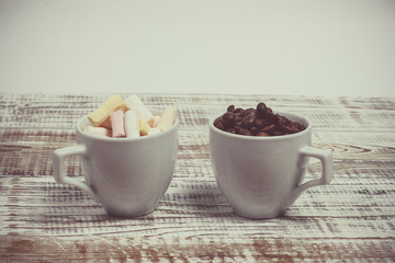 Cup with marshmallows and a cup with coffee beans