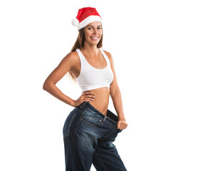 Fit, beautiful, young woman in oversize pants and Santa's hat, isolated on white background