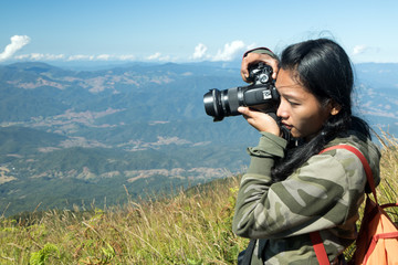 Woman photographs at the prospect of sky background. Girl with a camera on top of the mountain.Traveler photographs in the mountains.