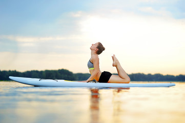 Woman on sup board practicing cobra yoga pose