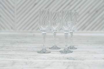 Empty glasses stand on a white wooden background