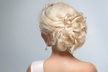 A smart wedding hairstyle on a blonde woman on a gray background.
