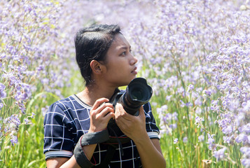 Woman with a camera the middle of the meadow with violet flowers Murdannia Giganteum. Photographer in nature.