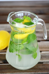 Jar of cool mint homemade lemonade on wooden table in a hot summer day