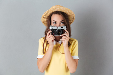 Lovely young girl in hat holding vintage camera at her face
