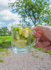 a Cup of cool drink of mint and lemon in hand.