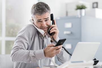 Stressed businessman having multiple calls