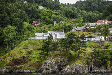 The landscape of cottages on a rock among the greenery off the coast of Norway