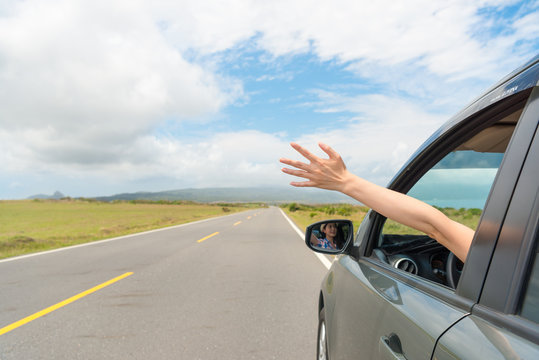 girl sitting on travel car happily reach out hand