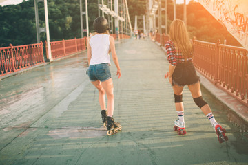 Two slim and sexy young women and roller skates. One female has an inline skates and the other has a quad skates. Girls ride in the rays of the sun