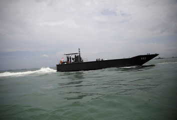 A Singapore patrol boat is seen in the waters near USS John S. McCain after a collision, in Singapore waters