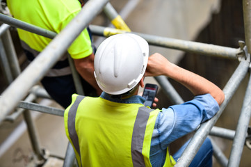 Workers inspecting construction works on a scaffold