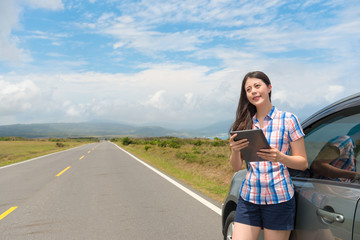 smiling beautiful female traveler holding pad