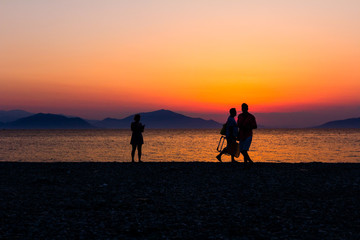 Silhouetted shot of sunset with couple, people by the beach