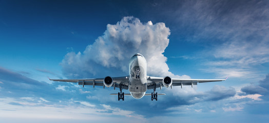 Tuinposter Vliegtuig Beautiful airplane. Landscape with white passenger airplane is flying in the blue sky with clouds at overcast day. Travel background. Passenger airliner. Business trip. Commercial plane. Aircraft