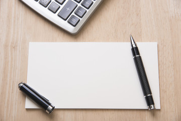 Blank paper with pen on wooden office desk.