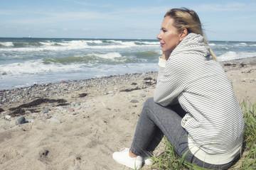 beautiful blond woman sitting on the beach