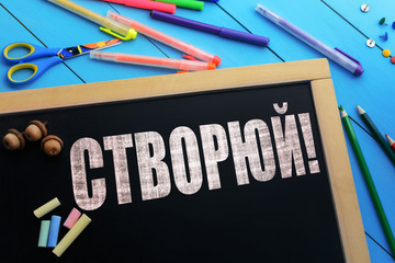 The text Create (on ukrainian) on a black chalkboard on the table with school accessories (pens, pencils, brushes)