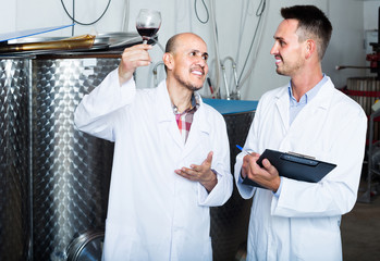 two men coworkers in white coats working in fermentation section