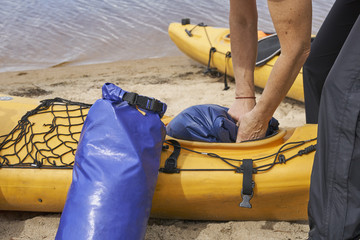 Woman hiker inserting a waterproof bag with the things into the kayak