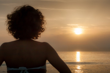 Silhouette of young woman practicing yoga on sandy beach at sunset.