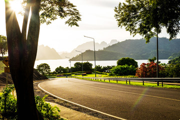 Quiet road beside big lake in upcountry when sunset in the evening , golden light effect