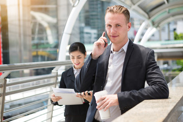 smile caucasian business man use smart phone talking with asian secretary help