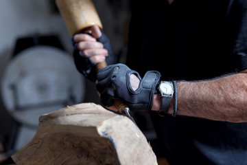 Close up of senior sculptor hands working on his sculpture in his workshop.
