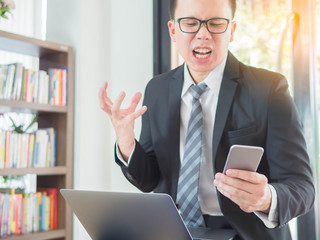 businessmen angry shouting to mobile phone and laptop at work office