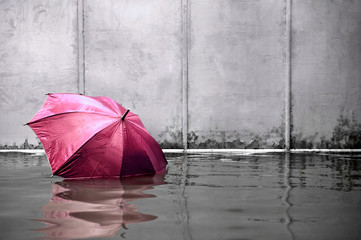 Pink umbrella floating concept. Flooded on street. .Waiting for help me after the rain. Black and white colors. Close up.