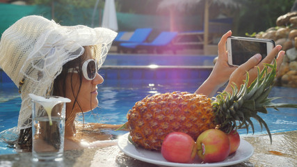 Young pretty woman wears sunglasses and hat takes selfie with mobile phone in swimming pool next to the glasses of the water and plate with tropical fruits.