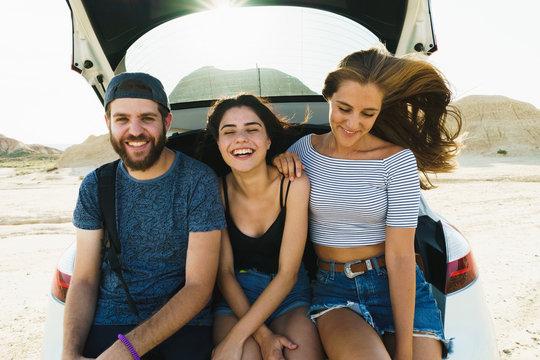 Friends sitting in car trunk