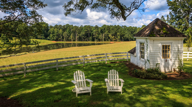 2 Adirondack chairs sit on a lawn in front of a white fence under a broad tree. There is also a pump well house to the right. Beautiful trees, a pond and clouds with a blue sky are in the background