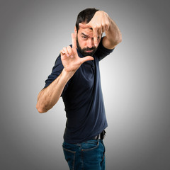 Handsome man with beard focusing with his fingers on grey background