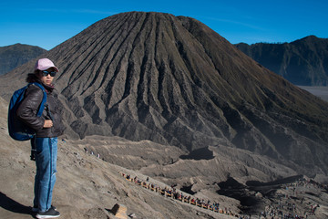 Woman tourism at top of crater view point at Mount Bromo volcano, view behind is Mount Batok JAVA, INDONESIA.