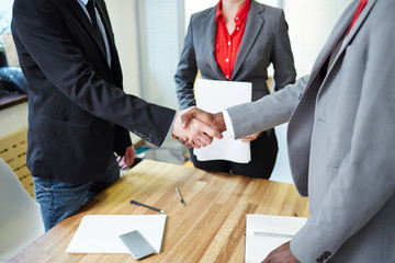 Successful business partners handshaking after signing contract