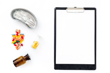 Doctor's workplace in clinic. Clip pad, colored pills and cuvette with ampoulie on white background top view mockup