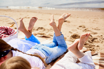 Bare feet of three little girls relaxing by seaside