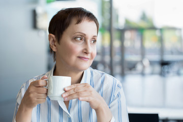 Woman with a coffee cup sitting in a cafe looking out of the window in the morning/lunchtime.Nice portrait/headshot of middle aged older businesswoman drinking hot coffee. Blurred office background.