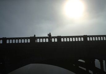 Tourists take pictures on a bridge as the sun emerges through fog cover before the solar eclipse in Depoe Bay
